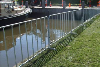 The crowd control barriers are installed on the bank of the river.