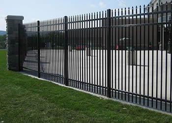Black steel picket fencing are used to safeguard a factory.